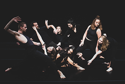Eight BFA dance students, dressed in all black, performing various movements in a semi circle.