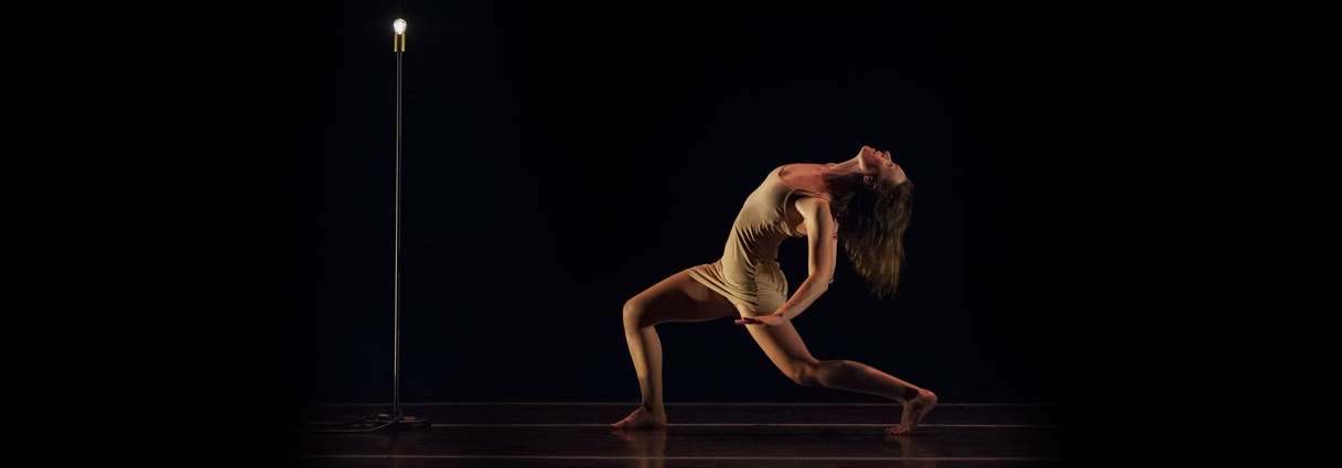 One dancer in a lunge on stage